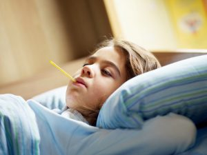 young girl lying down in bed with thermometer in her mouth