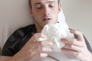 man in bed with a pile of tissues