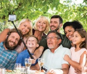 family taking picture with selfie stick