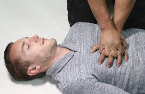 person giving CPR to man lying on the ground